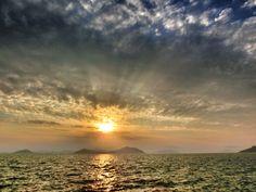 10 July 18:48 雲間から光りを放つ博多湾の夕陽です。