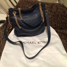 Authentic Michael Kors Jet Set Medium size MK Jet set used not new no rips but it has a stain at the bottom of the bag and a small pen Mark!! dust bag included!! Cute navy color great shape bag!! Trade value higher Michael Kors Bags