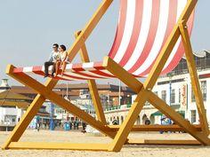 ANGLETERRE – Jeudi 22 Mars, les habitants de Bournemouth ont eu une énorme surprise sur leur plage. Une chaise longue 8,5 mètres de haut et 5,5 mètres de large fut installée pour faire la promotion des boissons Pimms. Une oeuvre du sculpteur Stuart Murdoch. manychefsbroth.co.uk