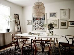 Dining room with a small gallery wall, wishbone chairs, and a IKEA bamboo pendant light