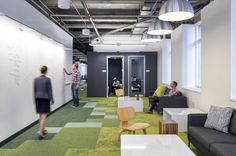 white board collaborative space green carpet black walls exposed ceiling
