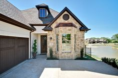 Village Homes: Cream painted brick with stone accent and dark brown trim and garage door.