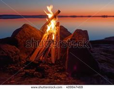 Stock Photo: Fire and flames of atmospheric campfire on the beach at night. Still water of the lake on the backgound with warm colors of sunset. Very shallow dept of field.