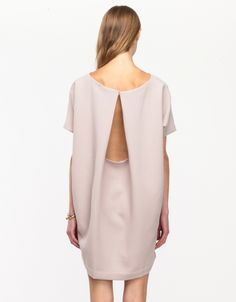 Minimal and clean, easy fit mini dress from Kaarem. Features draped open back styling with button closure at the back of neck, and a simple, low-key front.   •Textured mini dress •Open back styling •Button closure at back of neck •Cutout open