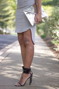 Great Mix of Textures With the Grey Dress, Black Leather Heels, And Metallic Clutch