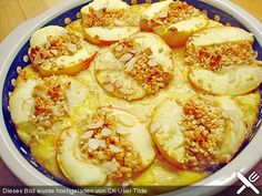 4 große Äpfel 8 EL Mandel(n), gehackte 80 g Honig 5 m.-große Ei(er) 10 EL Sahne 2 EL Honig 1 EL Haferflocken   Butter, für die Form   Mandel(n), gehobelt Video-Tipps      How To - Äpfel dünsten