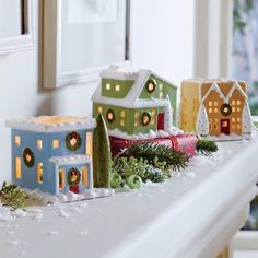 """VILLAGE SQUARE TEALIGHT TRIO The windows of our quaint, snow-covered cottages glow with the light of a tealight, sold separately. Set includes three hand-painted ceramic houses, each with a tealight dish. 2¾""""-3""""h."""