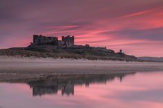Bamburgh Castle Sunset Reflections - long exposure photo taken to the south side of the castle at sunset reflected in the large pool of water on the sand.
