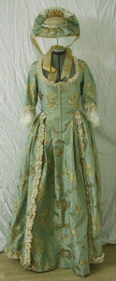 Exquisite 18th-century gown with hat. Pale blue-green patterned fabric with lace trim.