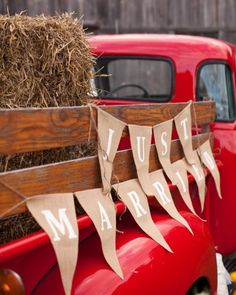 "An old red truck adorned with a ""just married"" sign makes a great backdrop for photos"