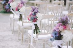 White chairs decorated with fresh flowers and white ribbons | Photography by http://www.roncaglioneweddingphotographers.com/