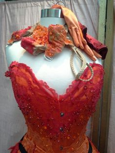 Red and orange burlesque corset, bejewelled with 100's of crystals. Matching net bra, g-string and gloves also showing, by Corsets by Nasty Ginny.