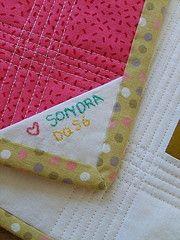 simple quilt label - no excuse not to make a label like this! Embroider name & date on a square, fold into triangle and put in when doing the binding - simple, lasting, wonderful....