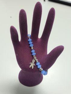 Pulsera de piedras azul cielo con pequeños remaches entre ellas y un pequeño niño de plata. Perfecta para cualquier ocasión.