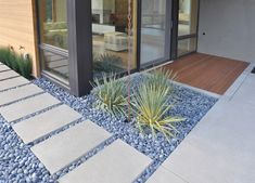 The stones in this garden add texture to the design and contrast against the smooth concrete