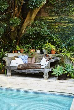 Weathered carved daybed with colorful patterned pillows.