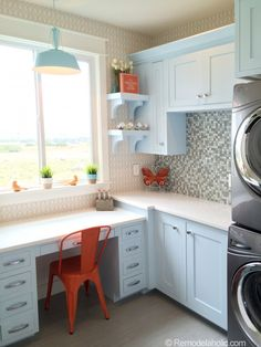 Laundry and work/craft room with light blue cabinets, orange accents, stainless washer and dryer