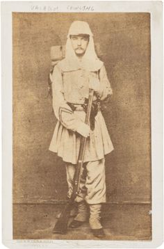 """The soldier in this photograph is seen in a full length studio portrait, wearing a Zouave or """"chasseur"""" style uniform and havelock. His stripes can be clearly seen on his right forearm and he holds a rifle in his hands. He is identified as Valentine Cowling and """"Valadon"""" Cowling on the mount. John Pierre Valadon Cowling, Jr. was a first lieutenant in the Kentucky State Guard in Louisville. He was one of five signatories to a recruiting document dated April 16, 1861, found on the person of accused spy John C. Brain, captured in Michigan City, Indiana in September 1861. Brain was accused of being a member of the Knights of the Golden Circle, but was released the next year after signing a loyalty oath."""