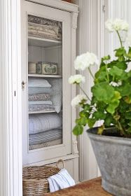 Painted White - beautiful cabinet with a glass front door is completely transformed with a few layers of white paint - via VIBEKE DESIGN