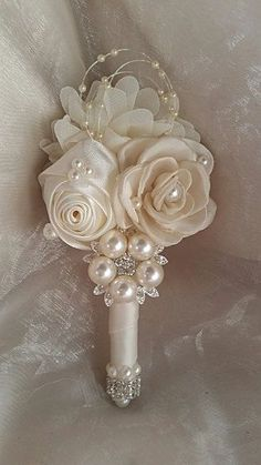 Ivory Satin Grooms Custom Designed Boutonniere - $45.00 ea  Can be made in custom colors also. - Custom Design exclusively by Elegant Wedding Decor by JoAnne Can Also be made and added onto custom Bouquet orders also. Contact for more details..... Production time on Boutonnieres - 10 days. THANK YOU  JoAnne- Designer/Owner Elegant Wedding Decor by JoAnne AKA: Glam Bouquet