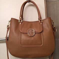"""Tory Burch """"Amanda"""" Hobo bag in Leather. NWT REDUCED!!!  GORGEOUS """"Royal Tan"""" pebbled Leather in the Classic Amanda Hobo versatile design. Can be carried with the 2 leather handles or worn as a Crossbody with detachable leather strap. Front large pocket with a magnetic closure and TB metal emblem. Back of bag has a large slip pocket adorned with gold nailheads. Inside has 1 large zipper pocket and 2 slip pockets. All gold hardware including gold medal feet. Measurements: 14""""L X 11""""H X…"""
