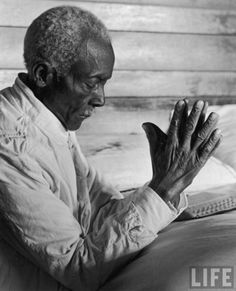Alfred Eisenstaedt - Old African American sharecropper Dave Alexander saying his evening prayers as he kneels at bedside at home, Mississippi, 1937