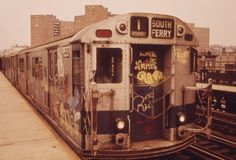 The 1 train covered in graffiti.