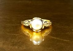 This stunning antique pearl ring would be perfect for any collection. Crafted with 14k rose yellow gold, this dainty gold ring features a gorgeous natural light gray - blue pearl and a beautiful artisan Arts and Crafts - Art Nouveau flower design. This natural pearl ring would make a unique antique