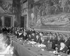 Beneath a fresco of The Horatii and Curatii by D'Arpino, statesmen of six European countries sign treaties for a European Common Market and European Atomic Pool. Seen here from left to right are Belgian Foreign Minister Paul Henri Spaak (extreme left), French Foreign Minister Christian Pineau (third from left), West German Chancellor and Foreign Minister Konrad Adenauer (center, signing) and his undersecretary Walter Hallstein (second from right), and Italian Prime Minister Antonio Segni.