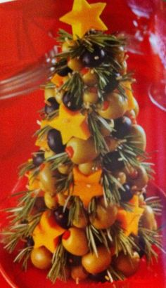 Cute Christmas appetizer! Use a styrofoam cone, olives, cheese cut with canape cutters, some rosemary sprigs, etc and make a beautiful and tasty appetizer to serve!