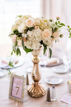 Tall ivory + peach floral centerpiece idea - lush ivory + peach roses, hydrangeas, and ranunculus displayed in vintage gold vessels + framed table numbers {Marianne Wiest Photography}