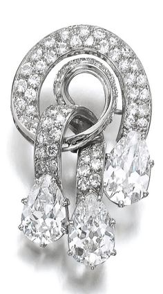 An Art Deco diamond brooch, 1930s. Of scroll design, set with brilliant-cut diamonds and three pear-shaped diamonds weighing 3.01, 3.25 and 3.46 carats, French assay marks. #ArtDeco #brooch