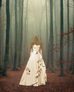 Woman with a face of leaves & wearing a white gown standing in the woods