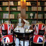 dens/libraries/offices - gold French chairs union jack flag black accent table white black zebra rug glass cloches glossy ebony wood floors built-ins bookshelves green paper backdrop Phrenology Head