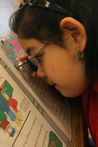 girl using magnifier to see her schoolwork
