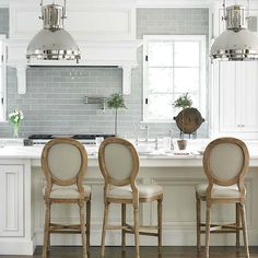Amazing kitchen design with Bottega Tiles blue glass tiles backsplash, pot filler, Ralph Lauren Montauk XL Pendants, white kitchen cabinets & kitchen island with marble countertops and Calypso counter stools.