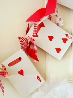 Queen of Hearts Garland  I LOVE, LOVE, LOVE this garland! Take a deck of cards and use only the hearts. Hole punch two holes at the top and string them all together with festive ribbon. Then you can add on extra fun, festive ribbon to spruce the garland up a little! SO UNIQUE!