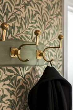 trompe l'oeil wallpaper with green leaves plant motifs, wall of an entrance, white door frame, with vintage reseda wooden coat rack and gilded metal elements with large shiny balls Source by archzinefr Coat Hanger, Wall Hanger, Scandinavian Wallpaper, Wooden Coat Rack, Brass Hook, Wallpaper Decor, White Doors, William Morris, My Dream Home