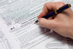 Person filling out a W-4 form - Jeroen Geeraert/Getty Images