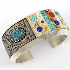Sterling Silver Cuff Bracelet with a Mosaic Inlaid Design using Fossilized Ivory, Coral, Sugilite, Lapis, 14k Gold, and Natural Turquoise from the Candelaria and Nevada Blue Mines. The Tufa Cast panel
