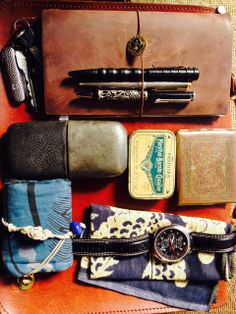 """Midori Traveler's Notebook Smith & Wesson Tactical Pen Parker Ballpoint Artex Dragon Pen Cigarette Case """"Menthol-Borate-Cocaine Pastille"""" Case repurposed as first aid kit Granddad's flask [[MORE]] Timberland Watch Handerkerchief Kimono wallet Swiss Army pocket knife w/ keychain"""