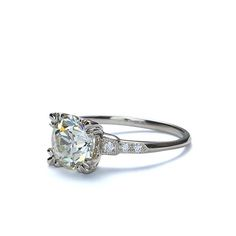 """Replica 1940s diamond engagement ring. A Golden Old European Cut Diamond weighing 1.86 cts and certified by the GIA as O-P color and VVS2 clarity (Report #2175896691) is set in a """"fishtail prong"""" crown, accented with six diamonds set into the stepped millegraine edged shoulders ( .06 cts, GH/VS). An exact replica of an original 1940s era engagement ring. 14K white gold. Size 5.75"""