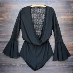 Gorgeous front wrap black romper featuring a crochet lace hem, sheer lace upper bell sleeves, deep v-cut neckline, and a sheer lace back. Model is wearing our w