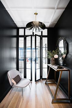 To reference the wall of windows in the living room, Brent installed iron-and-glass doors off the kitchen to create an intimate entry   archdigest.com