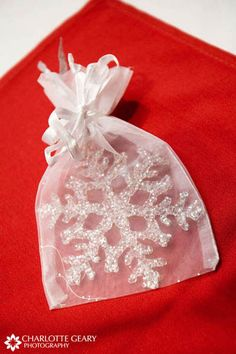Snowflake Christmas ornament as wedding favor. This is actually really cute. That way every year, the guests at the wedding will remember that day!