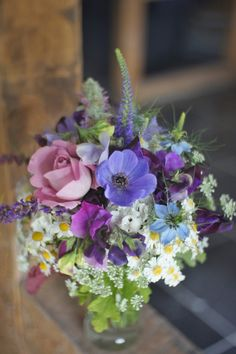 Purple bouquet on rustic wooden beams.