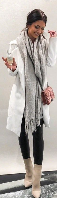 #spring #outfits woman in white coat with black pants and beige boots standing near white wall. Pic by @nicolecarlsonxo