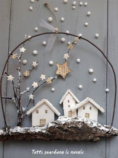 I just love this little vignette wreath idea! Driftwood, wire, little flat houses and paper stars..... Small Christmas decorations ... landscapes whitewashed to hang. http://tuttiguardanolenuvole.blogspot.it/2014/12/con-corteccia-e-filo-di-ferro.html
