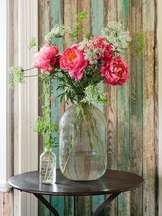 A jug holds peonies and Queen Anne's lace. The pine walls are original.