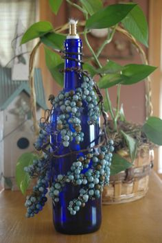 "Blue Grape Delight tiki candle! This cobalt blue wine bottle tiki torch is decorated with blue ""grapes"" and is great for your patio, porch or any table outside! This candle comes with a tiki torch wick for outdoor use only! Fill with citronella oil."